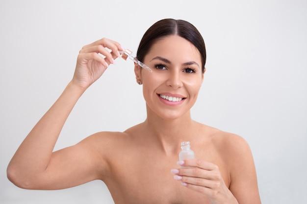 Giovane donna graziosa che ottiene trattamento speciale della pelle al salone di bellezza. ragazza che applica il siero dell'occhio.
