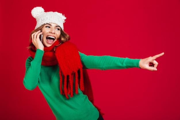 Giovane donna graziosa che parla indicando del telefono.