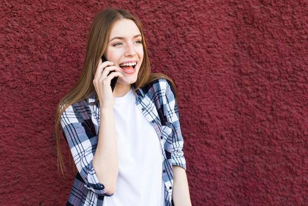 Giovane donna graziosa che parla sul cellulare con la bocca aperta contro la parete rossa