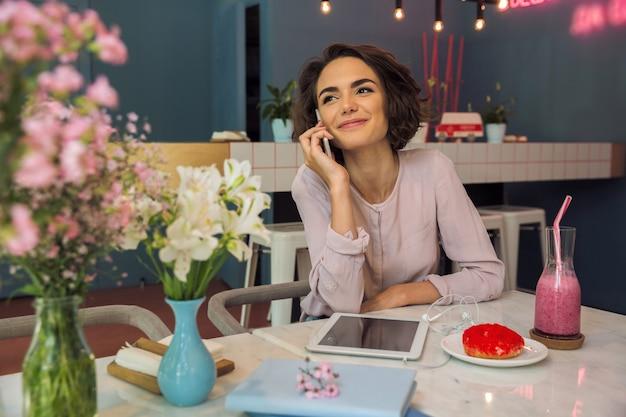 Giovane donna graziosa che parla sul telefono cellulare mentre sedendosi