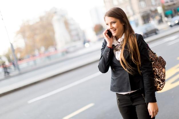 Giovane donna graziosa che parla sul telefono cellulare