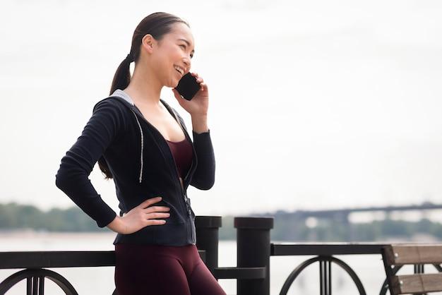 Giovane donna graziosa che parla sul telefono