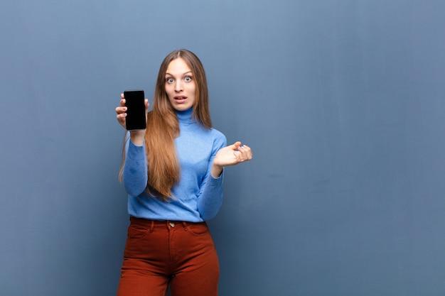 Giovane donna graziosa che per mezzo di uno smart phone contro la parete blu con uno spazio della copia