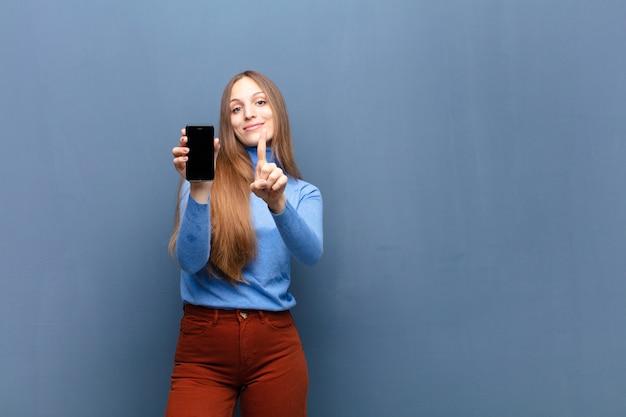 Giovane donna graziosa che per mezzo di uno smart phone