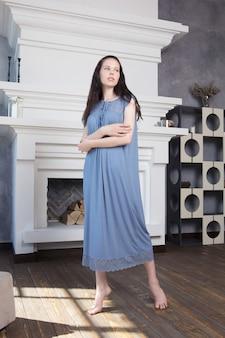Giovane donna graziosa che posa a casa in una camicia da notte blu