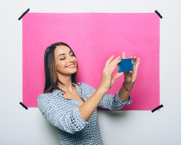 Giovane donna graziosa che prende immagine con il telefono della macchina fotografica