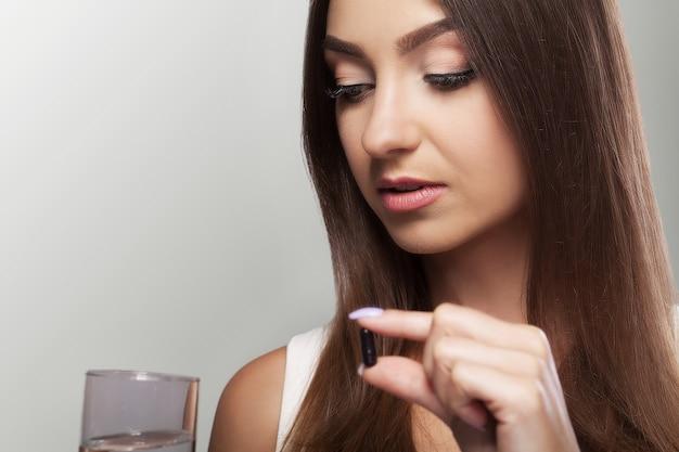 Giovane donna graziosa che prende una pillola nera e tiene un bicchiere d'acqua.