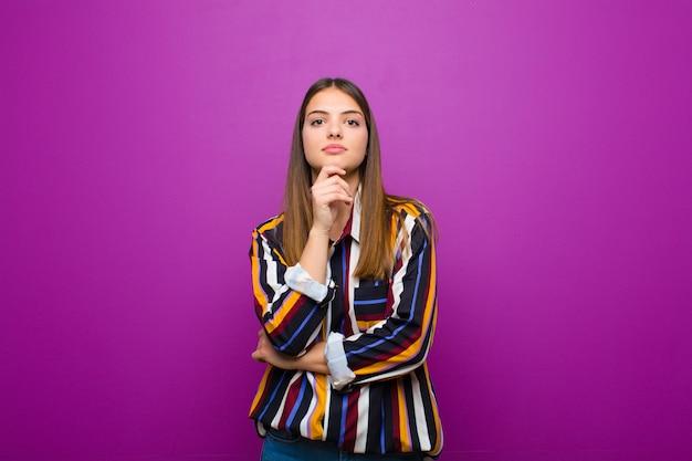 Giovane donna graziosa che sembra felice e che sorride con la mano sul mento, chiedendosi o facendo una domanda, confrontando le opzioni sopra la parete viola