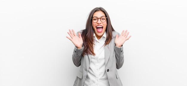 Giovane donna graziosa che sembra felice ed eccitata, scioccata da una sorpresa inaspettata con entrambe le mani aperte accanto al muro bianco isolato viso