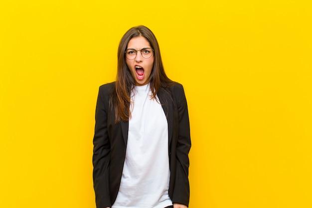Giovane donna graziosa che sembra scioccata, arrabbiata, infastidita o delusa, a bocca aperta e furiosa contro la parete arancione