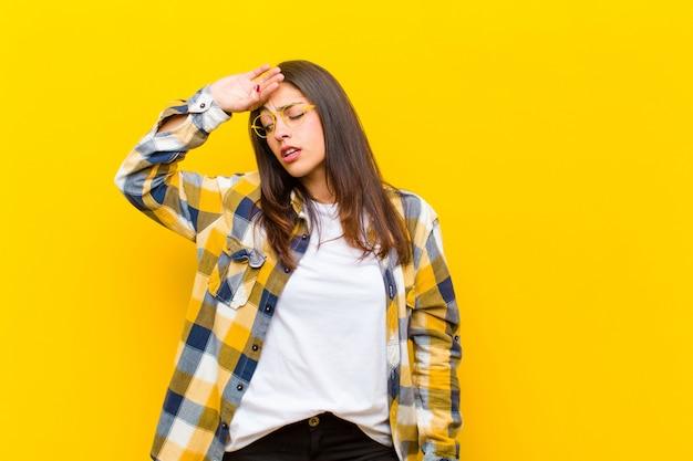 Giovane donna graziosa che sembra stressata, stanca e frustrata, asciugando il sudore dalla fronte, sentendosi senza speranza ed esausta contro la parete arancione