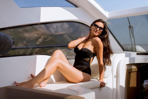 Giovane donna graziosa che si rilassa sull'yacht al giorno soleggiato