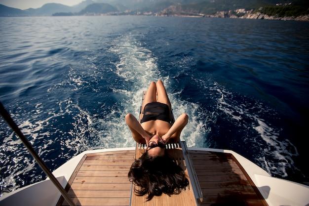 Giovane donna graziosa che si rilassa sullo yacht sul mare al giorno soleggiato