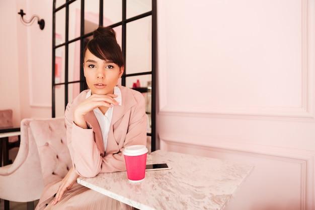 Giovane donna graziosa che si siede al caffè