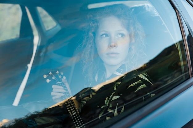 Giovane donna graziosa che si siede in macchina