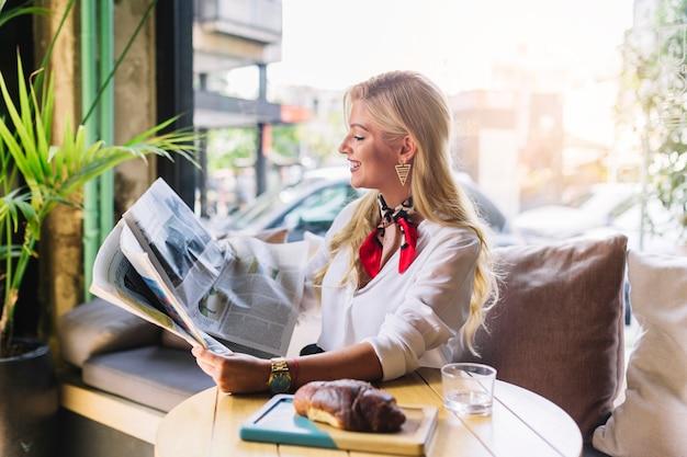 Giovane donna graziosa che si siede nel caffè che legge giornale
