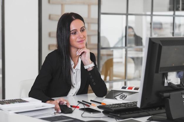 Giovane donna graziosa che si siede nell'ufficio