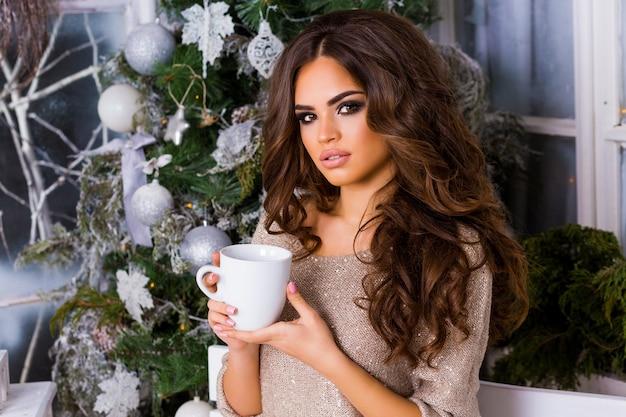 Giovane donna graziosa che sogna e beve caffè o tè, godendo la mattina di natale, close up ritratto di bella signora in abiti caldi e accoglienti seduti sulla terrazza decorata con luce