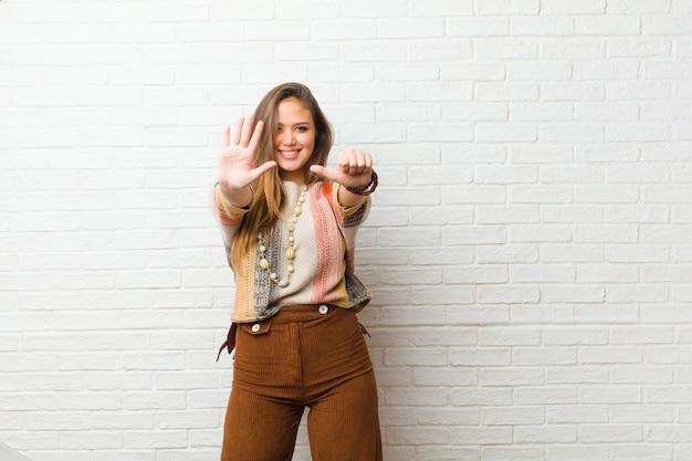 Giovane donna graziosa che sorride e che sembra amichevole, mostrando numero sei o sesto con la mano in avanti, conto alla rovescia