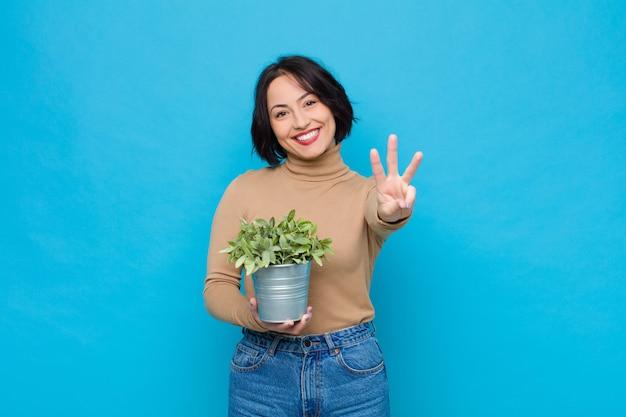 Giovane donna graziosa che sorride e che sembra amichevole, mostrando numero tre o terzo con la mano in avanti, conto alla rovescia con una pianta