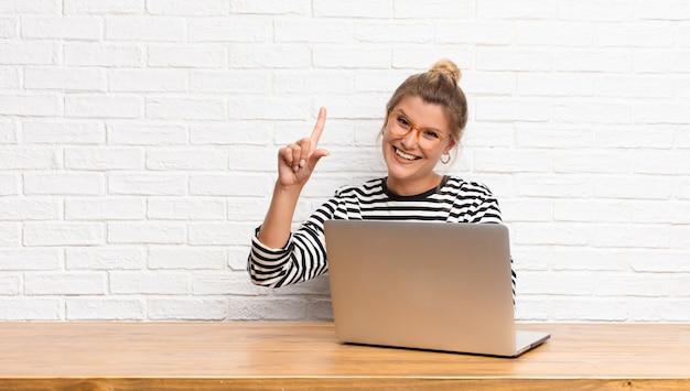 Giovane donna graziosa che sorride e che sembra amichevole, mostrando numero uno o prima con la mano in avanti, contando alla rovescia seduta con il suo computer portatile