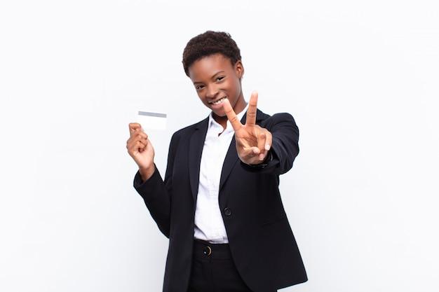 Giovane donna graziosa che sorride e che sembra vittoria felice, spensierata e positiva, gesturing o pace con una mano che tiene una carta di credito