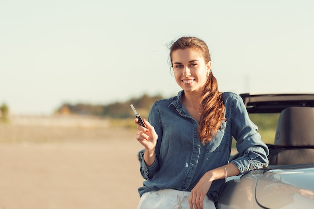 Giovane donna graziosa che sta convertibile vicino con le chiavi a disposizione