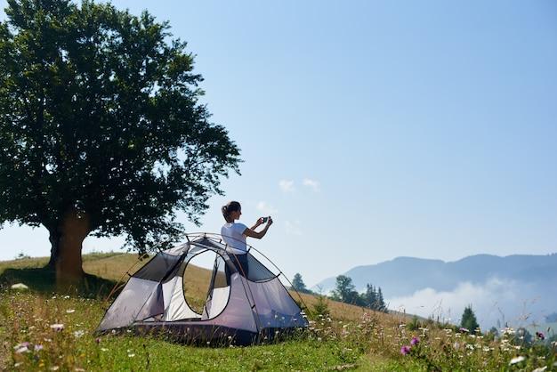 Giovane donna graziosa che sta sulla ripida collina erbosa alla piccola tenda turistica e al grande albero e che prende immagine di belle montagne nebbiose coperte di foresta sotto il chiaro cielo blu sulla mattina luminosa dell'estate.