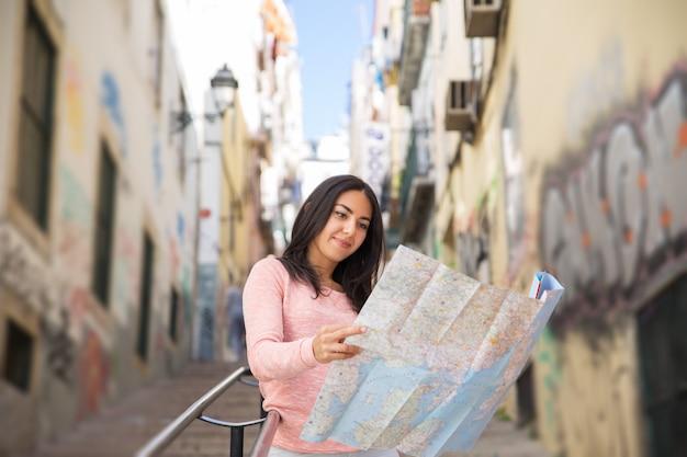 Giovane donna graziosa che studia mappa di carta sulle scale della città