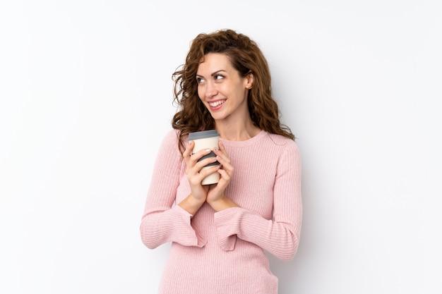 Giovane donna graziosa che tiene caffè da portare via