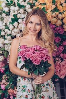Giovane donna graziosa che tiene il mazzo delle rose rosa a disposizione