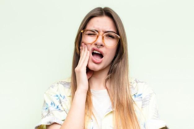 Giovane donna graziosa che tiene la guancia e che soffre di mal di denti doloroso, sentirsi male, miserabile e infelice, in cerca di un concetto di turista dentista