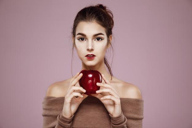 Giovane donna graziosa che tiene mela rossa in mani.