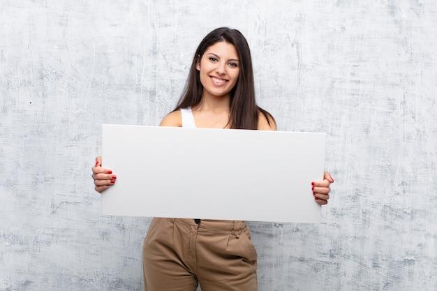 Giovane donna graziosa che tiene una bandiera contro la parete del grunge