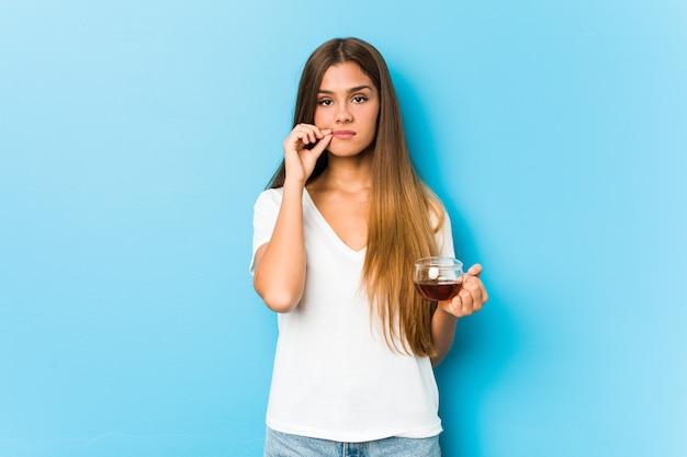Giovane donna graziosa che tiene una tazza di tè con le dita sulle labbra che mantengono un segreto.