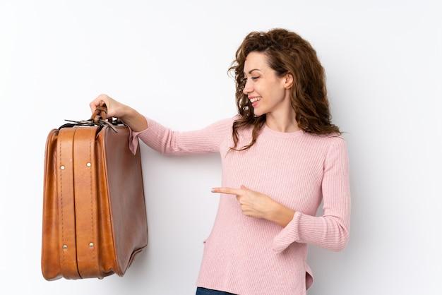 Giovane donna graziosa che tiene una valigetta vintage