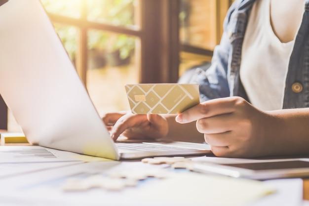 Giovane donna graziosa che utilizza una carta per comprare vestiti e cosmetici con laptop.