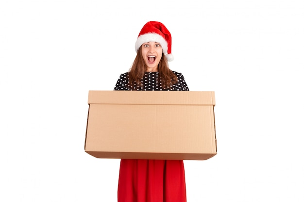 Giovane donna graziosa colpita e sorpresa che tiene il grande contenitore di regalo del cartone. isolato