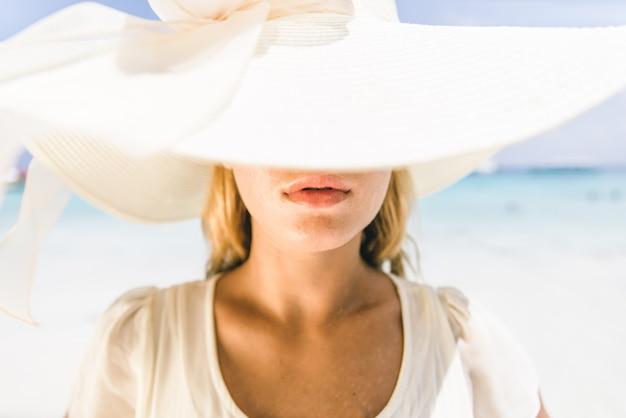 Giovane donna graziosa con cappello sulla spiaggia