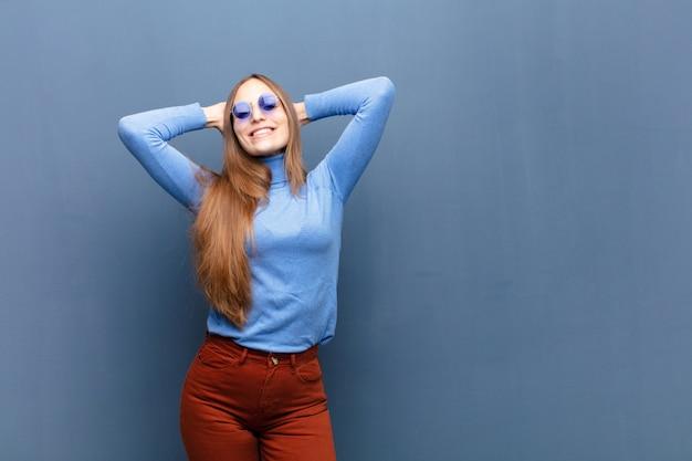 Giovane donna graziosa con gli occhiali da sole contro la parete blu con uno spazio della copia