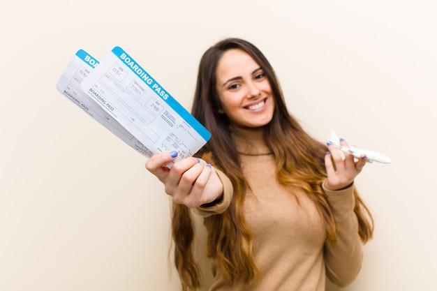 Giovane donna graziosa con i biglietti di una carta d'imbarco dell'aereo