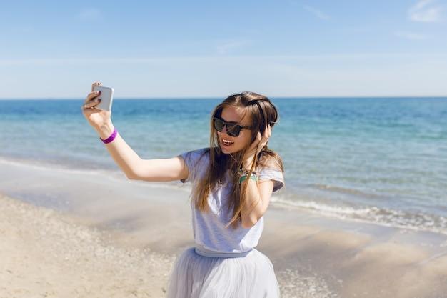 Giovane donna graziosa con i capelli lunghi è in piedi vicino al mare blu