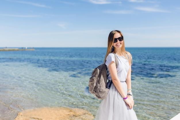 Giovane donna graziosa con i capelli lunghi è in piedi vicino al mare