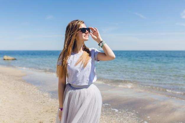 Giovane donna graziosa con i capelli lunghi sta camminando sulla spiaggia vicino al mare