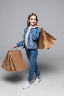 Giovane donna graziosa con i pacchetti di acquisto sulla parete grigia