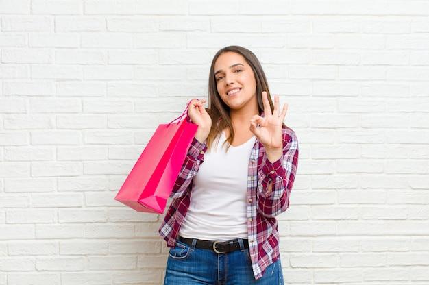 Giovane donna graziosa con i sacchetti della spesa contro la struttura del muro di mattoni