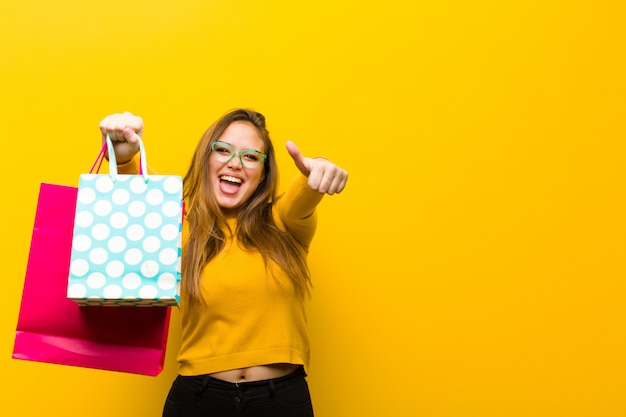Giovane donna graziosa con i sacchetti della spesa