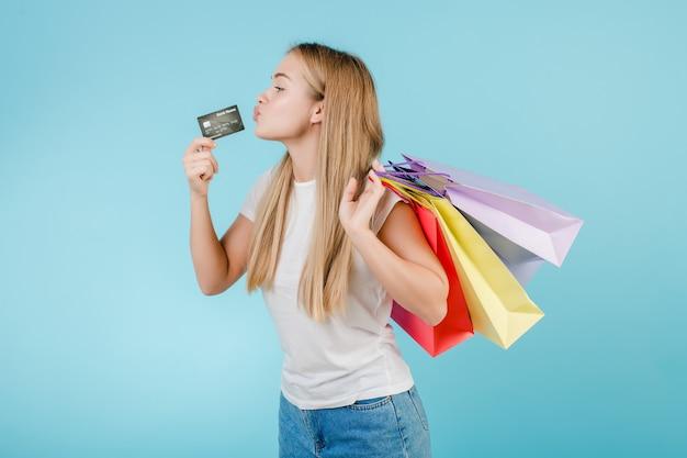 Giovane donna graziosa con la carta di credito e sacchetti della spesa variopinti isolati sopra il blu
