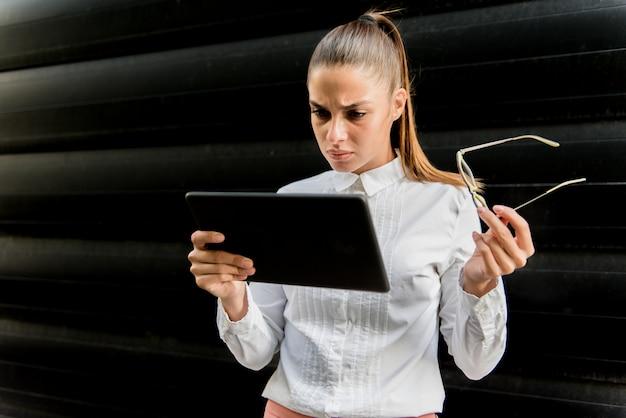 Giovane donna graziosa con la compressa digitale dall'edificio per uffici