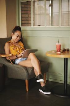 Giovane donna graziosa con la compressa digitale